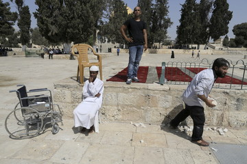 Palestinians clear stones after clashes between Israeli police and Palestinians in Jerusalem's Old City
