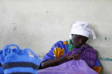 Woman sorts sheets of coloured polythene to be used for weaving polythene baskets at the community-based organisation Mirror of Hope in the Kibera slum of Nairobi