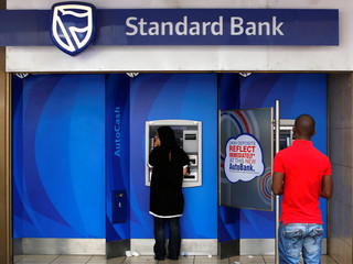 Customers queue to draw money from an ATM outside a branch of South Africa's Standard Bank in Cape Town