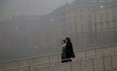 Women wearing masks walk as smog blankets Sarajevo