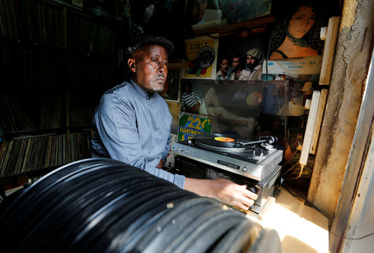 Vendor Rugami operates a record player inside his stalls that specializes in the sell of second-hand vinyl records and restoration of vintage players at the Kenyatta Market in Nairobi