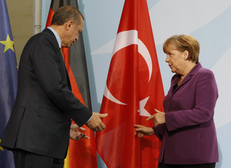 German Chancellor Angela Merkel speaks to Turkish Prime Minister Tayyip Erdogan as they address the media after meeting in the Chancellery in Berlin