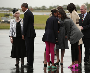 Sasha and Malia chat as U.S. President Obama is greeted upon their arrival on Air Force One in Belfast