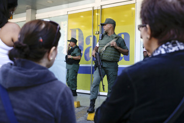 Members of Venezuela's National Guard stand guard outside a Daka store as shoppers wait to shop for electronic goods in Caracas