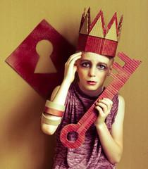 мальчик в картонной короне и картонным ключом на фоне замочной скважины