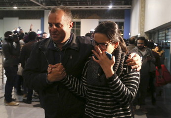 A passenger of EgyptAir flight 181 which was hijacked, embraces a family member after they arrived at Cairo international airport in Cairo