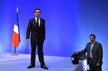 A bodyguard stands next to France's President Sarkozy after he delivered a speech during a visit in Ajaccio on the French island of Corsica