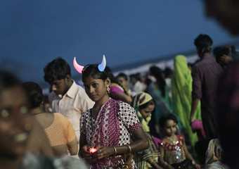 A woman wearing an illuminated devil's horn sells toys along a beach in Mumbai