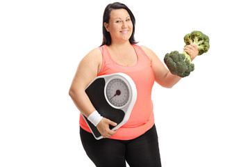 Overweight woman with weight scale and broccoli dumbbell