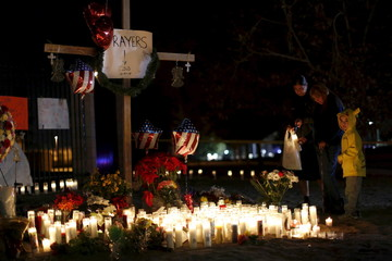 People stand by a pop-up memorial in San Bernardino, California December 4, 2015, following Wednesday's attack