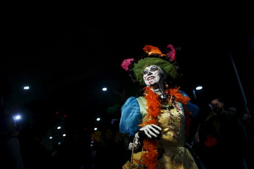 "A woman dressed up as ""Catrina"", a Mexican character also known as ""The Elegant Death"", smiles during a Catrinas parade in Mexico City"