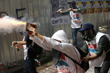 Protesters shoot firecrackers at riot police during a May Day demonstration in central Istanbul