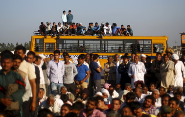 Demonstrators from the Jat community sit on top of a school bus as they block the Delhi-Haryana national highway during a protest at Sampla village