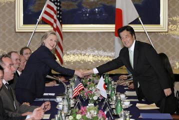 U.S. Secretary of State Hillary Clinton shakes hands with her Japanese counterpart Katsuya Okada before their meeting in Tokyo