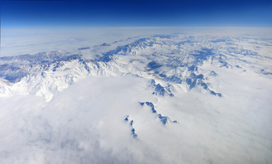 A beautiful panorama of snow-capped mountains with clouds