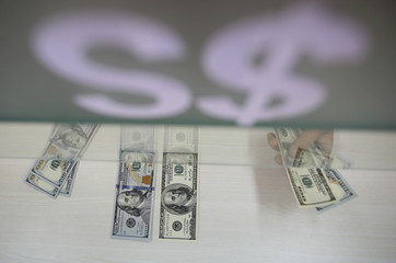 U.S. hundred dollar bills are seen at AYA Bank's money changer in Yangon