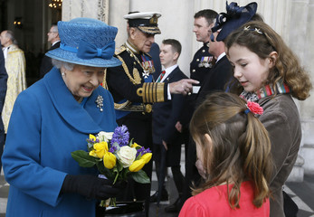 Britain's Queen Elizabeth receives a posy from Sophie Thorneloe, and sister Hannah Thorneloe, after attending the Service of Commemoration for Afghanistan, at St Paul's Cathedral in London