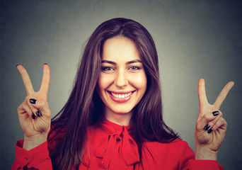 Smiling woman showing peace hand sign with both hands