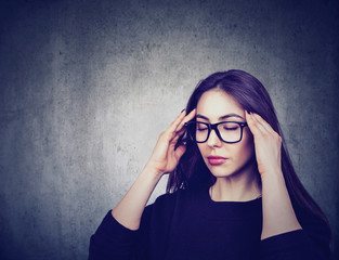 Stressed woman with glasses suffering from eyestrain having headache