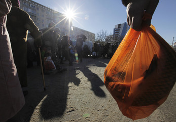 A customer carries a bag of fish at a wholesale market in Stavropol