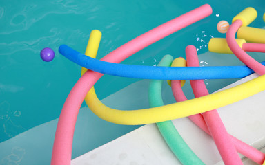 water aerobic equipment. colored aqua noodles in swimming pool.