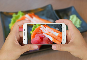 Hands taking picture of sashimi japan food with smartphone.