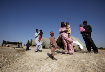 Villagers displaced by flooding stand outside their tents as they wait for food handouts at a relief camp for flood victims in Jamshoro