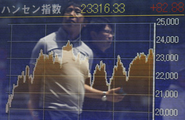 Passersby are reflected in electronic graph showing recent movements of Hang Seng Index outside a brokerage in Tokyo