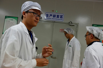"""Lab technicians prepare to go into the """"Mass production, research and development area"""" inside Sun Yat-Sen University-Michigan State University Joint Center of Vector Control for Tropical Disease in Guangzhou, China"""