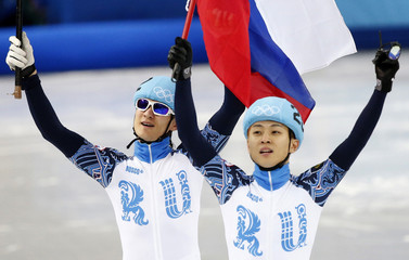 Winner Victor An and second-placed Vladimir Grigorev of Russia wave their country's flags after the men's 1,000 metres short track speed skating final event at the Iceberg Skating Palace during the 2014 Sochi Winter Olympics