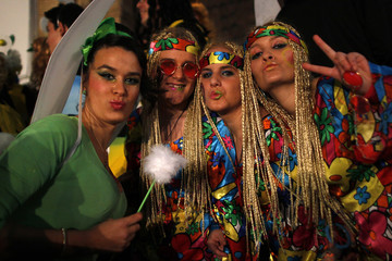 Revellers dressed up as a fairy and hippies pose for a picture as they take part in the New Year's celebrations in Coin
