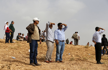 Turkish Kurds watch the Syrian town of Kobani from near the Mursitpinar border crossing