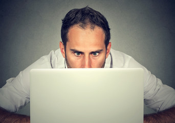 Man hiding behind a laptop staring at screen with a shocked face expression