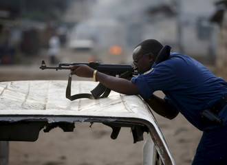A policeman aims his rifle before he shoots during a protest against Burundi President Pierre Nkurunziza and his bid for a third term in Bujumbura