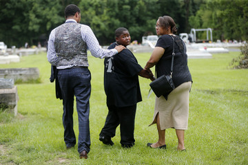 Na'Quincy son of Alton Sterling looks back at his father's grave as he leaves Alton's burial, at the Mount Pilgrim Benevolent Society Cemetery with family attorney Justin Bamberg and Na'Qunicy's grandmother whose name was withheld in Baton Rouge