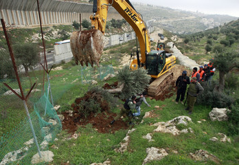 An Israeli soldier pushes a protester away as an excavator works on a section of the controversial Israeli barrier near Bethlehem