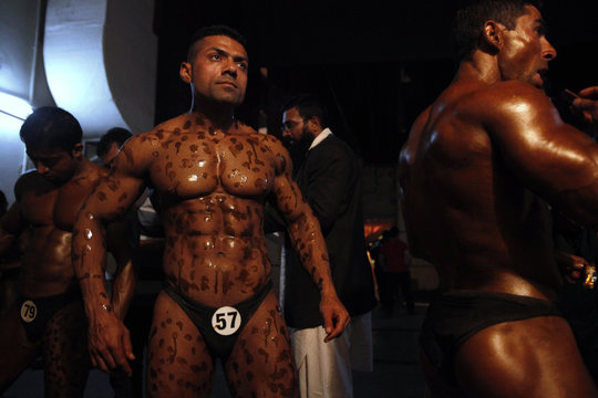 Competitors have tanning lotion applied on their bodies before taking part in the 10th South Asian bodybuilding championship in Lahore