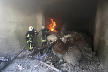 Civil Defence members try to put out a fire caused by what activists said was a barrel bomb dropped by forces loyal to Syria's president Bashar Al-Assad in Aleppo's al-Saliheen district
