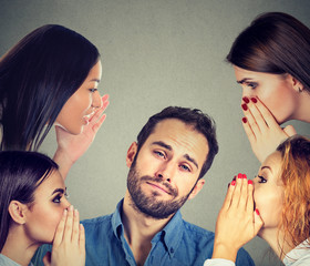 Four women whispering a secret latest gossip to a bored annoyed man