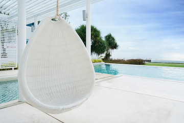 Relaxing white rattan hanging chair at swimming pool on sea view for vacation, summer and travel concept.