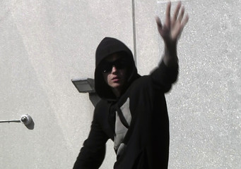 Pop singer Justin Bieber waves to fans as he leaves a jail after being released on bail in Miami