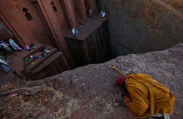An Ethiopian Orthodox monk prays within a rock hewn church ahead of Ethiopian Christmas in Lalibela
