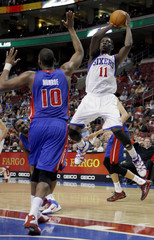 76ers guard Holiday shoots under pressure from the Pistons center Monroe during the fourth quarter of NBA basketball game action in Philadelphia Pennsylvania