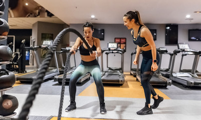 Woman doing battle rope exercise at gym