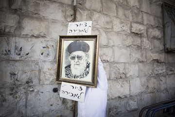 An Ultra-Orthodox Jewish man hangs a picture of Rabbi Ovadia Yosef to be sold during his memorial rally in Jerusalem