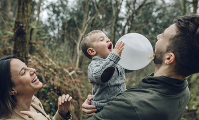 Happy family playing with a balloon in forest