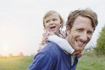 Vater mit Tochter huckepack