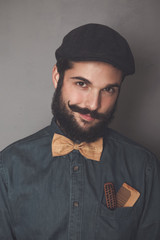 Portrait of bearded man wearing cap, denim shirt, cork bow tie, wearing wooden combs for beard and mustache in his pocket
