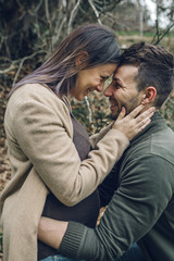 Man with smiling pregnant woman in nature