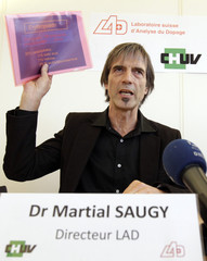Director of the Swiss anti-doping laboratory Martial Saugy holds papers of a presentation during a news conference in Lausanne